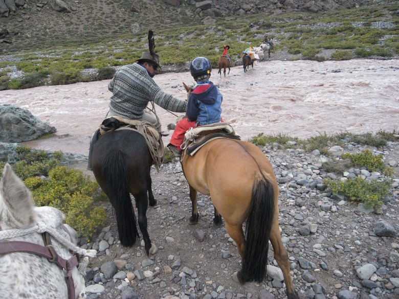 child rider on horseback crossing river